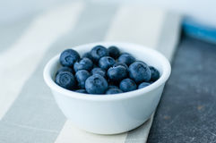 White bowl of blueberries. Small white bowl of blueberries linen tablecloth close up royalty free stock photos