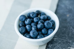 White bowl of blueberries. Small white bowl of blueberries linen tablecloth close up top view stock image