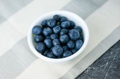 White bowl of blueberries. Small white bowl of blueberries linen tablecloth close up top view royalty free stock photos