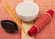 White bowl with boiled organic basmati jasmine rice with wooden chopsticks and sweet soy sauce on bamboo placemat background royalty free stock photo