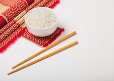 White bowl with boiled organic basmati jasmine rice with wooden chopsticks and sweet soy sauce on bamboo placemat with red linen royalty free stock photo
