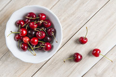 White bowl of cherries on the table Royalty Free Stock Photography