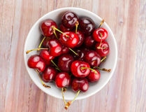 White bowl of cherries on wood. White bowl of sweet cherries on wood texture Royalty Free Stock Photography