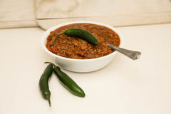 White Bowl of Chili with Two Jalapenos and One on Top Stock Images