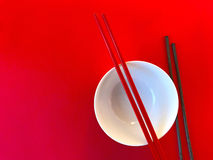 White bowl with chopsticks on red Royalty Free Stock Photo