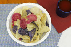 White Bowl of Colorful Potato Chips. Three different colors of potato chips with tomato juice. Colorful red white and blue chips made from Crimson, Purple royalty free stock photography