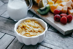 White bowl with corn Flakes and milk  and Fresh sliced fruit: ra. Spberry, kiwi, melon, oranges on a wooden background Royalty Free Stock Image