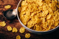 White bowl of corn flakes. On a rustic wooden surface royalty free stock photos