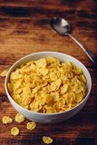 White bowl of corn flakes. On a rustic wooden surface stock images