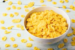 White bowl of corn flakes. On a wooden surface stock images
