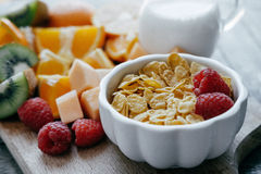 White bowl with corn FlakesCloseup White bowl with corn Flakes a. Closeup White bowl with corn Flakes and milk  and Fresh sliced fruit: raspberry, kiwi, melon Stock Images