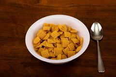 Crunchy Corn Cereal. A white bowl of crunchy, square corn cereal for breakfast on a wood table royalty free stock photos
