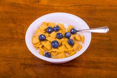 Crunchy Corn Cereal with Blueberries and Milk. A white bowl of crunchy, square corn cereal for breakfast on a wood table royalty free stock images