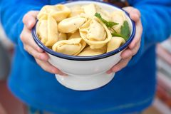 Bowl with ravioli in boy hands. White bowl with few fresh ravioli in boy small hands Stock Photos