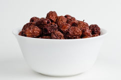 White bowl filled with dried red dates Royalty Free Stock Images