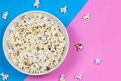 White bowl filled with popcorn on a blue and pink background royalty free stock photo