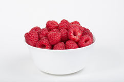 White bowl filled with raspberries Stock Images