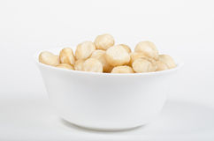 White bowl filled with roasted macadamia nuts Stock Images
