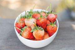 White bowl filled with strawberries. On old wood Royalty Free Stock Image