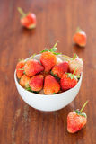 White bowl filled with strawberries on a wooden textured table. Top Stock Photo