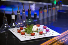 White bowl of fresh and healthy Mediterranean salad with mozzarella cheese, tomatoes and basil leaves. Stock Image