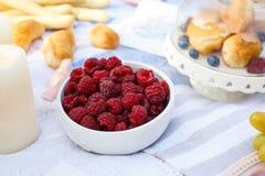 White bowl with fresh raspberry on white picnic blanket.  royalty free stock photo