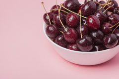 White bowl of fresh red cherries on a pink background. Copy space. close-up Stock Photo