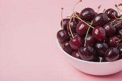 White bowl of fresh red cherries on a pink background. Copy space. close-up Stock Image
