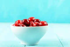 White Bowl Of Fresh Red Cherries On Turquoise Royalty Free Stock Photos