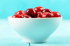 White Bowl Of Fresh Red Cherries On Turquoise Stock Image