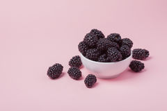White bowl of fresh red raspberries on a pink background. Copy space.  Stock Photos
