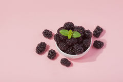 White bowl of fresh red raspberries on a pink background. Top view. Copy space. Hard light Stock Photo