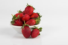 White bowl of fresh ripe red strawberries. White bowl of some fresh ripe red strawberries royalty free stock image