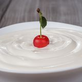 White bowl full of sour cream with cherry Royalty Free Stock Image