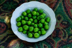 The white bowl full of turkish green plum stock photography