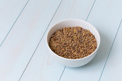 White bowl full of uncooked lentils. On blue wooden table Stock Images