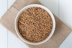 White bowl full of uncooked lentils. On blue wooden table Royalty Free Stock Image