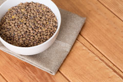White bowl full of uncooked lentils. On wooden table Royalty Free Stock Image