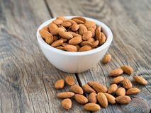 White bowl with a handful of nuts of almonds. On a wooden background table Royalty Free Stock Photo