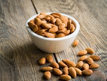 White bowl with a handful of nuts of almonds on a wooden background table. Image with shadow Royalty Free Stock Images