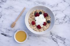 White bowl of muesli with raspberries and blueberries. White bowl of muesli with raspberries, blueberries, yogurt and a pot of honey Royalty Free Stock Images