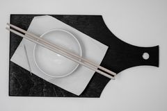 White bowl and napkin, toothpick, chopsticks on  black board stock photo