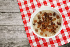 White bowl of oatmeal with raisins. On a checkered red and white linen fabric lying on the old wooden background. Diet food, Great Lent, Great Fast. View from stock image