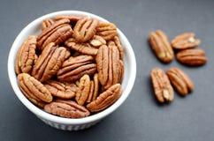 White bowl of pecan nuts Stock Photos