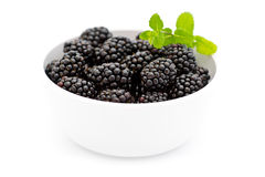 White bowl with pile of fresh blackberries and green mint - isolated Stock Photo