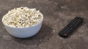 Bowl of popcorn and remote control on a wooden table stock image