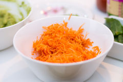 White bowl of shredded carrots against background of dinner tabl Stock Photos