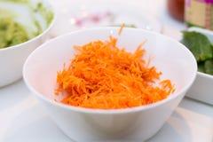 White bowl of shredded carrots against background of dinner tabl. E blurred Stock Photos