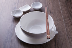 White bowl, spoon, sauce bowl and chopsticks on wood table Royalty Free Stock Photos