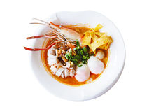 White bowl of Tom Yum Kung with noodles and seafood isolated stock photography